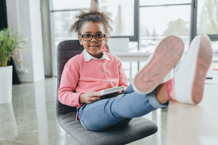 smiling african american businesswoman with legs on table looking at camera in office 版權商用圖片