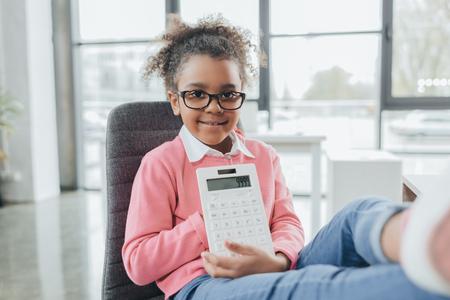オフィスで座っている間アフリカ系アメリカ人実業家表示電卓 写真素材
