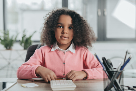 african american businesswoman with curly hair working with calculator in office