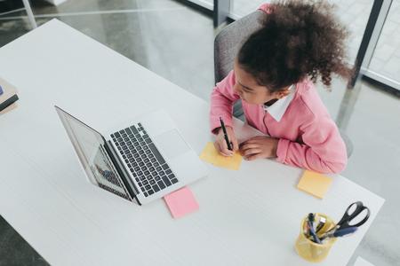 テーブルにノート パソコンとノートを使用してアフリカ系アメリカ人の女の子