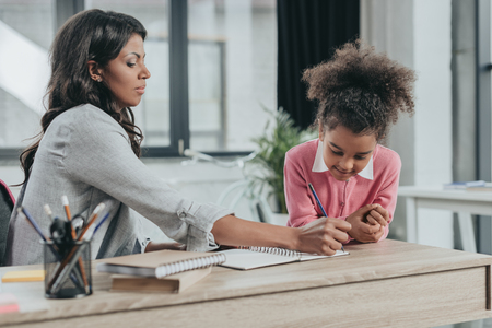 mother helping little daughter doing homework Stock Photo