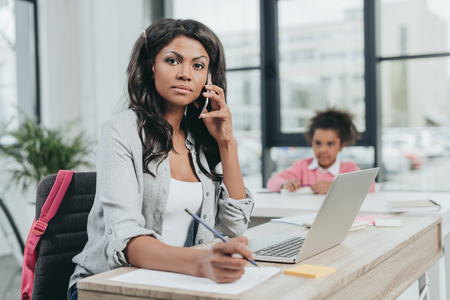 businesswoman talking on smartphone while sitting at workplace