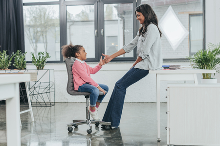 businesswoman playing with daughter at workplace in business office