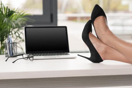 businesswoman legs crossed on table near laptop and eyeglasses