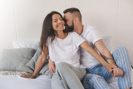 young couple smiling and embracing in bed at home