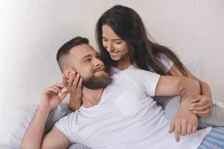 glimlachend vriend en meisje die en op bed thuis omhelzen liggen