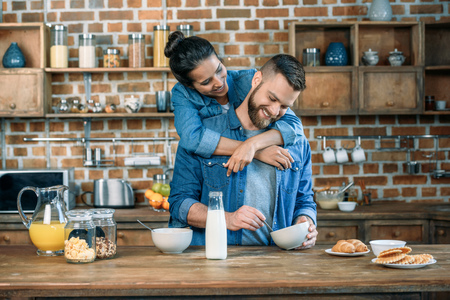 young woman hugging handsome bearded man having breakfast at home