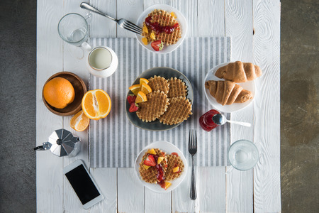 fresh tasty breakfast with waffles, coffee and smartphone with blank screen on table