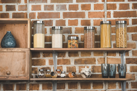 various cereals and spices in glass containers on wooden shelves