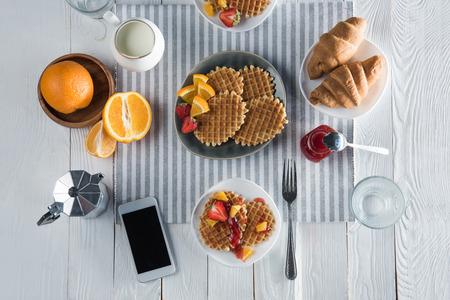 Desayuno sabroso fresco con gofres, café y teléfono inteligente con pantalla en blanco sobre la mesa Foto de archivo - 83698973