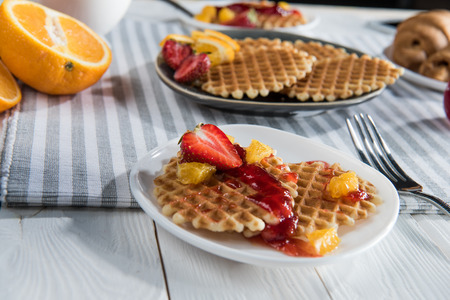 fresh homemade waffles with fruits and jam on table