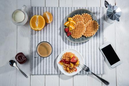 Petit déjeuner savoureux avec des gaufres et smartphone avec écran blanc sur la table Banque d'images - 83698979