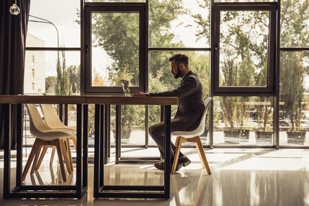窓の前のテーブルに座ってラップトップを使用しての実業家 写真素材