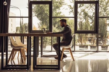 창 앞의 테이블에 앉아있는 동안 랩톱을 사용하는 사업가 스톡 콘텐츠 - 83698983