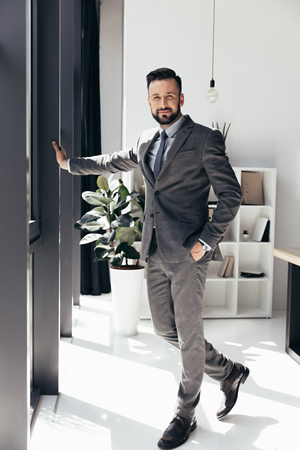 bearded businessman in suit posing with hand in pocket at modern office