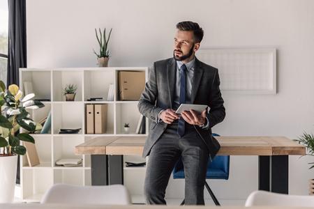 bebaarde peinzende zakenman met behulp van digitale tablet in moderne kantoor