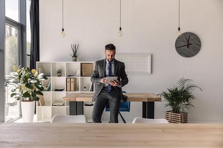 현대 사무실에서 디지털 태블릿을 사용 하여 수염 된 집중 사업가