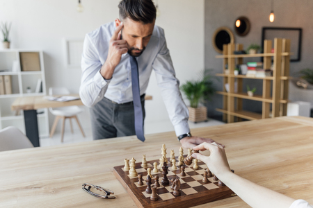 businessman playing chess with colleague in office