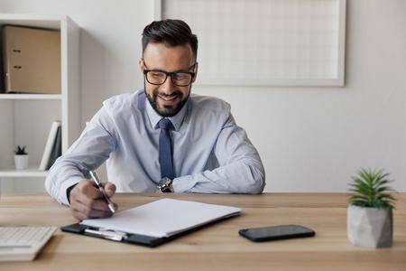 alegre, hombre de negocios, con, pluma, mano, Mirar, blanco, papel