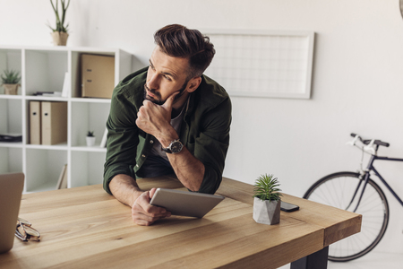 bearded man holding digital tablet and looking away in office Stock Photo