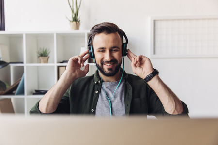 bearded man listening music in headphones while sitting in office