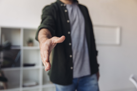 man reaching hand for handshake while standing in office Banco de Imagens