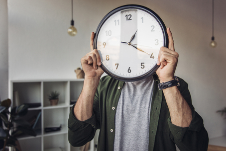 man holding wall clock while standing in office