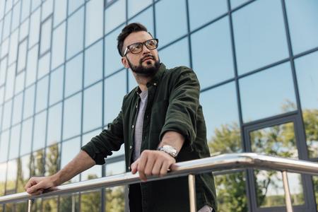 bearded man in eyeglasses leaning at railing at looking away Banco de Imagens