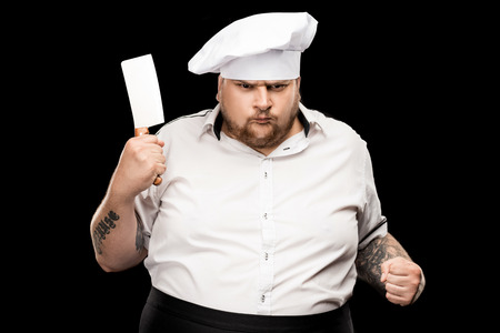 Angry young chef in hat holding meat knife and shaking fist Imagens