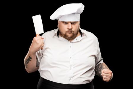 Giovane cuoco arrabbiato in cappello con coltello di carne e pugno agitando Archivio Fotografico - 83702515