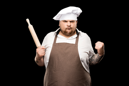 Angry young chef holding rolling pin and shaking fist