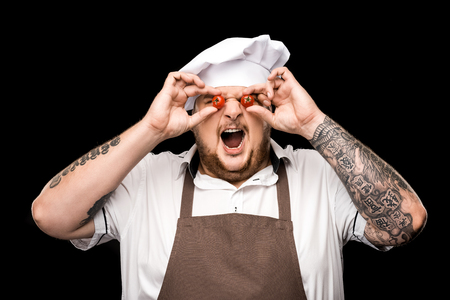 chef in hat and apron holding cherry tomatoes and grimacing Stok Fotoğraf