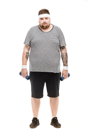 chubby caucasian man holding dumbbells and looking at camera