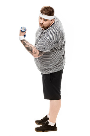 fat man flexing biceps with dumbbell and looking at camera
