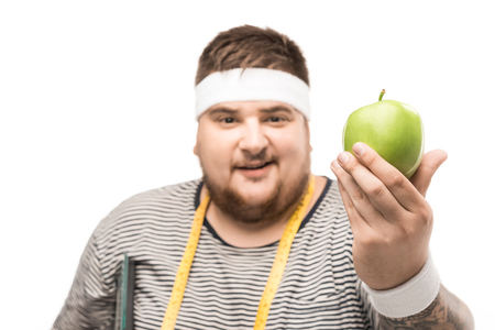 portrait of young chubby man with measuring tape holding apple Stok Fotoğraf