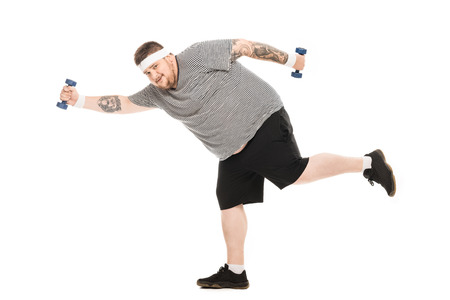 young obese man running with dumbbells and looking at camera