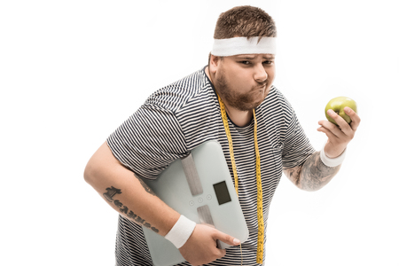 fat man holding body scales and apple with upset facial expression Stock fotó