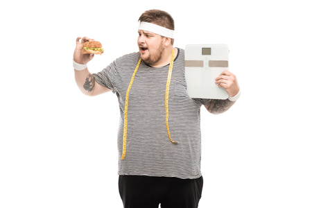 fat man holding body scales and burger