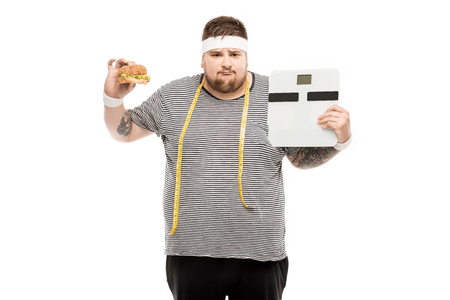 upset fat man holding body scales and burger