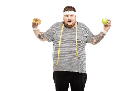 fat man holding burger and apple with facial expression