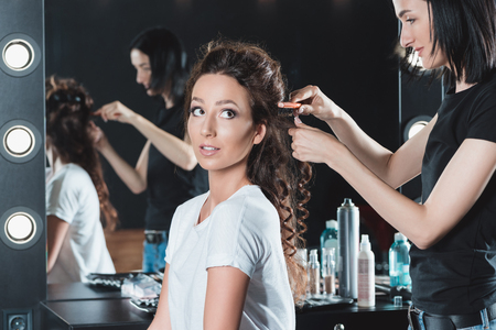 woman getting hair brushed by hairstylist in beauty salon