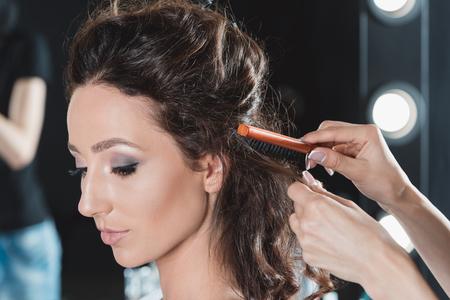 女性のビューティー サロンのヘアスタイリストによるブラシの髪を取得