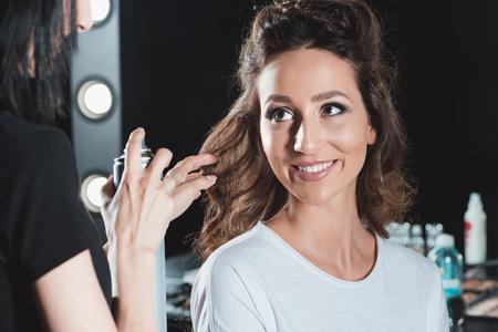 ヘアスタイルの仕上げにヘアスプレーを使用して髪ドレッサー
