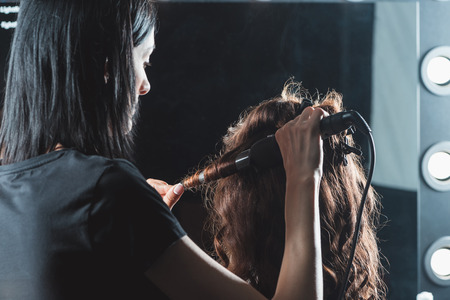 hair dresser using curling iron while styling hair