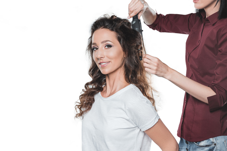 woman getting hair done by hair dresser isolated on white