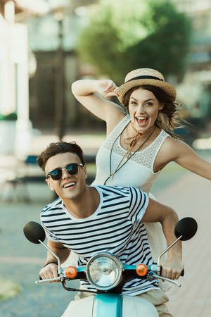 young stylish couple having fun and riding scooter in city