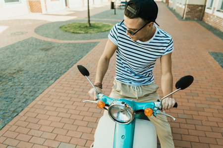 young man in cap and sunglasses riding moped and looking down