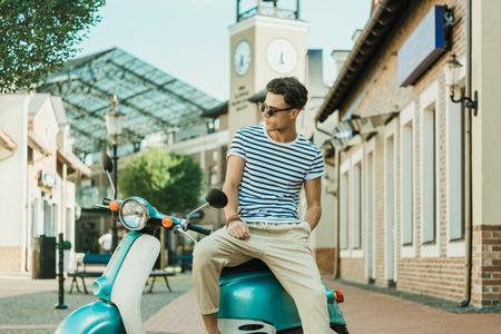 man sitting on retro scooter parked on street Stok Fotoğraf