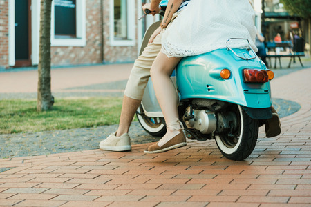 casual couple riding on scooter outdoors