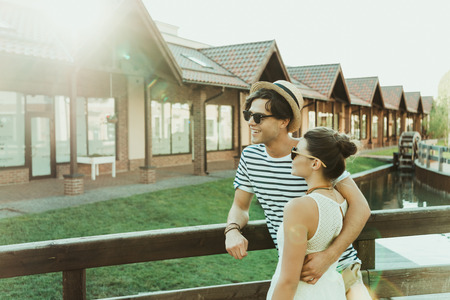 casual couple embracing and looking away while standing at bridge